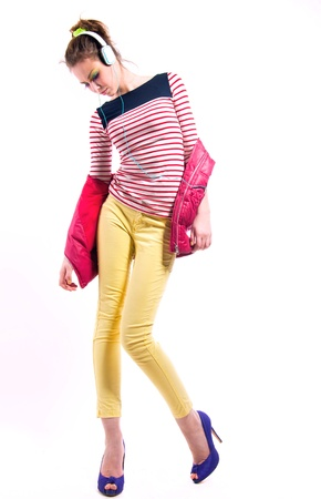 Pretty young girl isolated on white wearing bright casual clothes like yellow pants, stripped red white and blue shirt, pink vest,  purple high heels, listening to music via headphones and dancing. photo