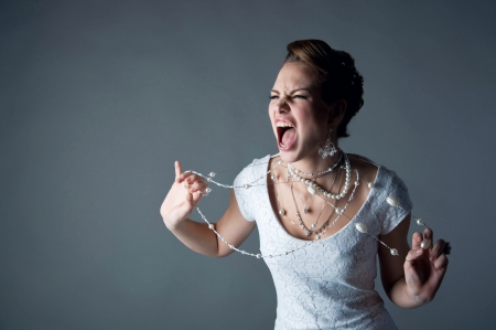 Studio portrait of beautiful angry shouting bride wearing white dress, screaming and crying at someone, trying to tear her pearl beads against gray background. Copy space. Stock Photo