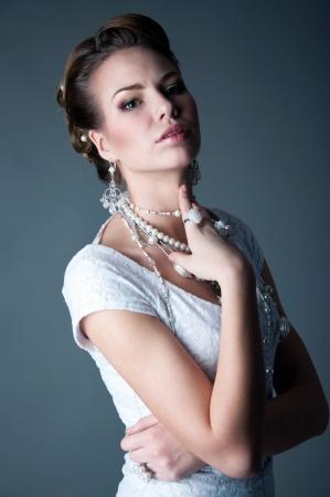 Low key studio portrait of pretty bride wearing white dress
