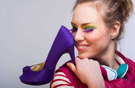 Studio portrait on gray of young beautiful fashion girl wearing bright colorful makeup with purple long eyelashes, green earphones, pink vest, holding a violet high heel shoe and looking with toothy smile. Copy space photo