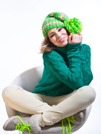 pompon: Happy funny girl wearing winter clothes knitted sweater, green yellow hat with pom-pon, sneakers with bright laces, sitting on white chair, smiling and laughing with toothy smile, hands and legs crossed. Isolated on white background. Copy space Stock Photo