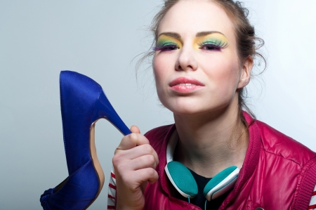 Studio portrait on gray of young beautiful fashion girl wearing colorful makeup with purple long eyelashes