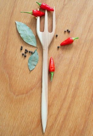 Still life of bunch of chili pepper, black pepper, nutmegs, peppercorn and bay leaves with wooden fork trident on the wooden texture table background photo