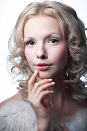 Studio portrait of beautiful young blond female model angel with curly hair, hazel eyes, wearing tender light makeup with red lips, top with feathers, holding her arm near her lips, looking thoughtfully at camera. Copy space, isolated on white background Stock Photo - 17644085