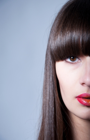 Beauty studio portrait of pretty young female model with straight hair, long straight fringe, natural makeup and bright colorful red glossy lips, looking at camera. Half face. Gray background, copy space Stock Photo - 17644083