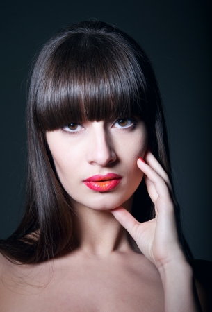 Beauty studio portrait of young pretty brunette female model with healthy long straight hair, long fridge, clear skin, elegant glamour makeup with slightly open glossy colorful red lips and coral nail, holding her hand near her mouth, looking at camera. C photo