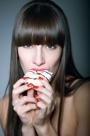 Beauty studio shot of sexy brunette female model with long straight healthy hair, glossy red lips, holding tasty donut with her hands, eating it with great pleasure and temptation, looking at camera. Black background Stock Photo