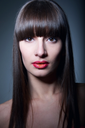 Beauty studio portrait of young pretty woman model with healthy long straight hair, long fridge, clear skin, elegant glamour makeup with slightly open glossy colorful red orange lips, naked shoulders, looking at camera. Gray background