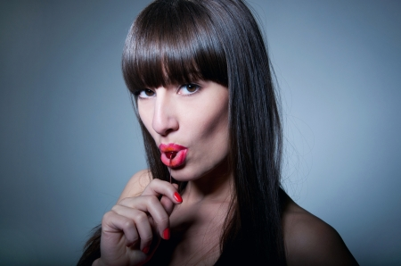 Glamour portrait of sexy woman model with natural makeup, long healthy shiny hair and long fringe, licking ripe fresh cherry and looking at camera with temptation. Gray background photo