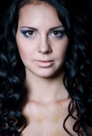 Facial studio portrait of pretty brunette woman model with shoulders, long shiny healthy black curly hair, elegant blue makeup, mouth slightly open, looking at camera