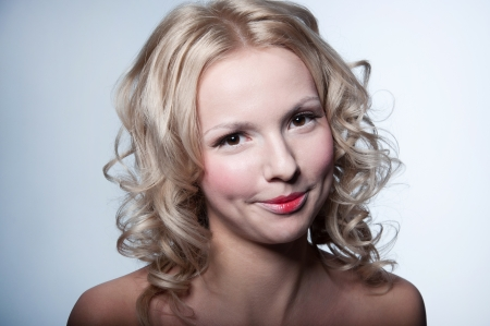 Studio portrait of happy smiling pretty blond woman model with curly hairstyle, tender daily makeup looking at camera. Gray background, copy space Stock Photo