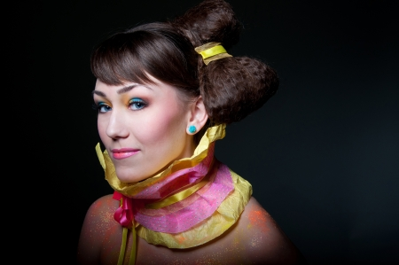Beauty glamour portrait of pretty woman model with colorful makeup, glossy lips, small rose earrings, extraordinary wrapping paper collar with ribbons, amazing hairstyle in form of a bow, looking at camera. Black background, copy space