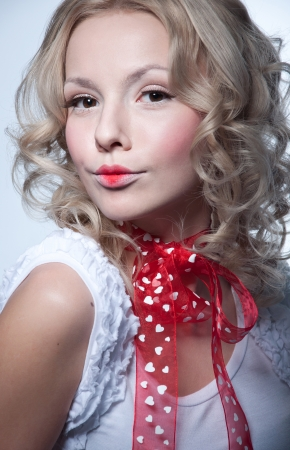 Beautiful young blond woman model with curly hair, hazel eyes, wearing tender light makeup with red lips, red transparent ribbon with hearts made into a bow on her neck, white top blouse with frill sleeves, looking at camera Stock Photo - 17893574