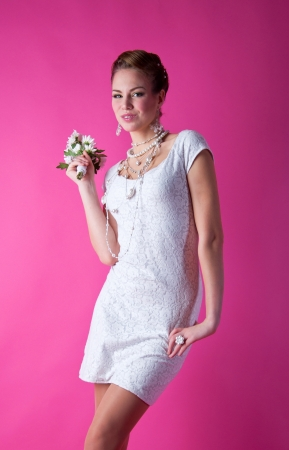 Pretty funny smiling bride girl wearing white lace wedding dress, pearls and beads, holding a bunch of flowers, having fun in studio and looking at camera with innocent but happy look against pink background