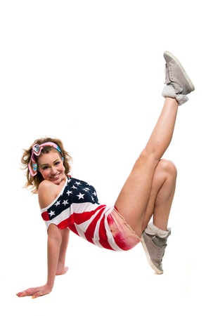 Full length portrait of beautiful young funny American patriotic girl wearing colorful pink blue head band, red shorts, off the shoulder top tank with USA flag, jumping, laughing, break dancing, going crazy, smiling at camera. Isolated on white, copy spac Stock Photo - 18290374