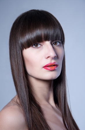 Beauty studio portrait of pretty young woman model with straight hair, long straight fringe, natural makeup and bright colorful red glossy lips half open, looking at camera. Gray background, copy space