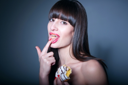 Pretty sexy brunette girl with long straight healthy hair, bare shoulders, glossy red lips, holding tasty doughnut with her hand, talking sweet cream from it and putting on her tongue, looking at camera. Black background, copy space
