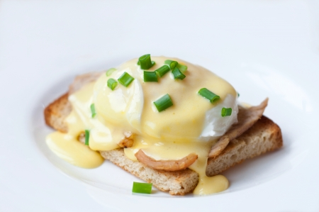 Traditional French breakfast dish eggs Benedict made of crust toast, chicken chop, poached eggs, Hollandaise sauce and decorated with green lettuce on white plate.