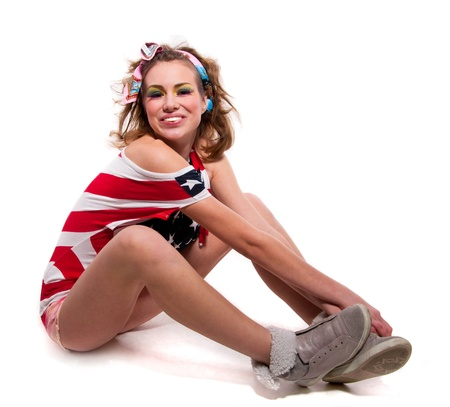 Full length portrait of beautiful young positive American patriotic girl wearing red shorts, off the shoulder USA flag top tank, sitting on the floor, arms and slender legs crossed, laughing, smiling, looking at camera  Isolated on white, copy space Stock Photo - 18385303