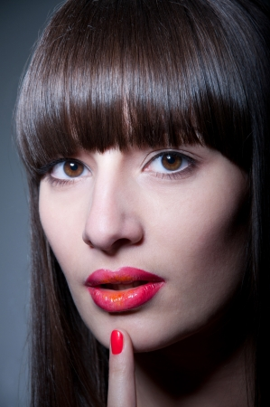 Beauty studio portrait of beautiful young woman model with long straight fringe, natural makeup, bright colorful red glossy lips and nail polish of the same color, holding her finger near lips, looking at camera. Gray background, copy space Stock Photo