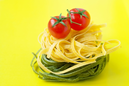 Colorful bright still life made of traditional Italian yellow and green pasta nests arranged one above the other, with two ripe fresh shiny red cherry tomatoes on top. Against yellow background, copy space photo