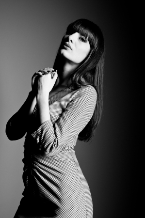 Black and white studio portrait of young beautiful woman model with head up, wearing checked dress, black nails, long straight hair with fringe, posing, holding hands near chest, looking at camera  Gray background, copy space photo