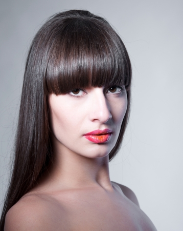 Beauty studio portrait of beautiful woman model with long straight fringe, natural makeup, bright colorful red glossy lips, looking at camera  Gray background, copy space photo