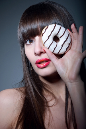 Pretty sexy brunette girl with long straight hair, bare shoulders, glossy red lips, holding tasty donut with hand as a monocle, looking at camera  Dark gray background, copy space