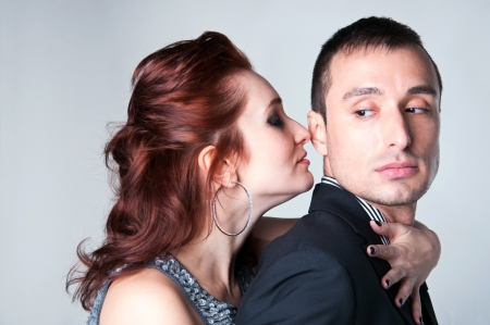Side view studio portrait of young beautiful passionate couple a man and a woman embracing each other, standing close, feeling desire and temptation  Gray background photo