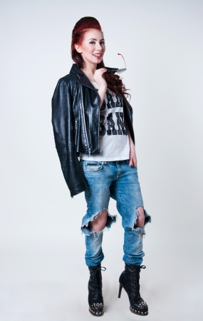Pretty young rocker woman model with cute red haircut, wearing leather jacket, ripped blue jeans, black boots with high heels and spikes, holding her glasses, looking at camera. Gray background, copy space photo