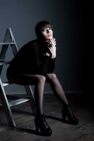 Studio portrait of confident beautiful slim woman model with awesome long legs wearing black body suit, boots with high heels, sitting on steps of staircase, looking at camera. Copy space photo