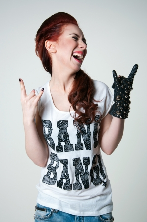 Pretty young emotional rock woman model with cute red haircut, wearing white top, ripped blue jeans, black leather glove with round metal rivets, shouting and screaming. Gray background photo