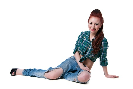 Pretty young woman model with long legs, wearing green checked shirt, ripped blue jeans, black high heels, with red hairstyle, sitting on the floor, smiling and looking at camera. Isolated on white, copy space photo
