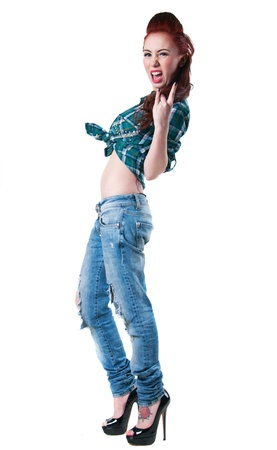 Pretty young woman model with long legs, wearing green checked shirt, ripped blue jeans, black high heels, with red hairstyle, standing, shouting loudly, smiling, looking at camera. Isolated on white, copy space photo