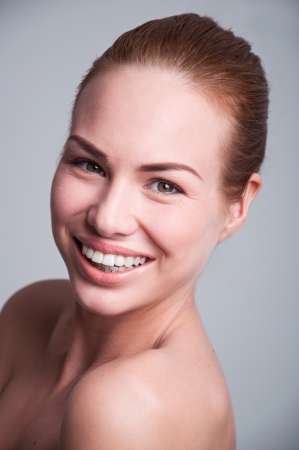 Studio shot of young pretty happy woman girl with big sincere toothy smile, having white teeth, clear skin, fresh look, wearing braces on her lower teeth. Gray background. photo