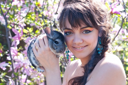 Beautiful young woman model with bright colorful makeup wearing blue earrings, holding her friend pet chinchilla on her hands close to her face, looking at camera. Against blooming trees