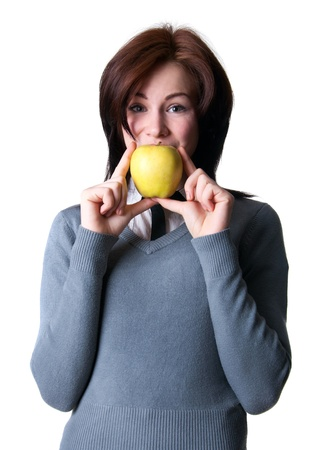 Pretty happy young college student woman model wearing gray pullover, striped shirt, holding ripe yellow apple in her hands, covering her mouth, looking at camera. Isolated on white, copy space photo