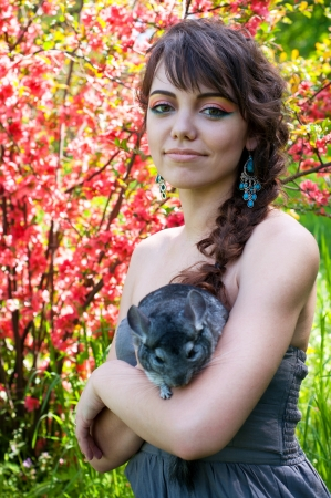 Pretty young woman model with bright colorful makeup wearing summer dress, blue earrings, holding her pet chinchilla on her hands, looking at camera. Against blooming trees photo