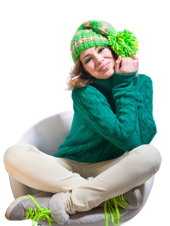 Young funny cute winter girl wearing green warm woolen knitted sweater, yellow green bright hat with pom pon, light pants, boots with bright laces, colorful makeup, looking happily with toothy smile at camera  Isolated on white background photo