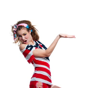 Beautiful young funny American pattic girl wearing colorful pink blue head band, red shorts, off the shoulder top tank with USA flag, shouting loudly, pointing at something, smiling at camera. Isolated on white, copy space Stock Photo - 19938098