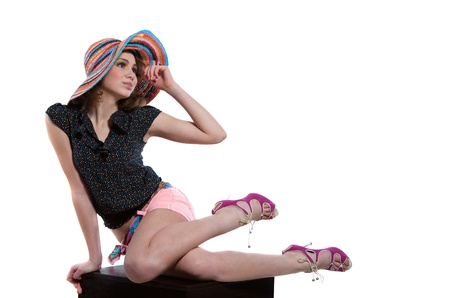 Young beautiful woman model wearing colorful wicker hat, top, shorts, pink high heels, sitting on cube, holding her hat with hand, looking forward with anticipation for vacation. Isolated on white, copy space photo