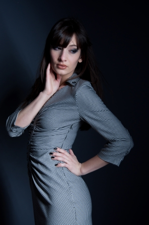 Studio portrait of young beautiful woman model wearing elegant checked black and white dress with buttons photo