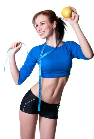 Slim sporty young woman model wearing blue top and black shorts, holding ripe apple Stock Photo