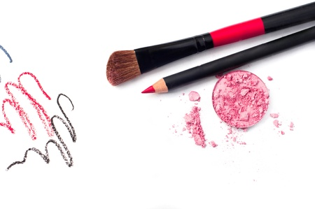 Still life of a small makeup kit light tender pink eyeshadow, red lip pencil, special professional brush for eye shadow applying, red, black and gray pencil strokes  Isolated on white background, copy space photo