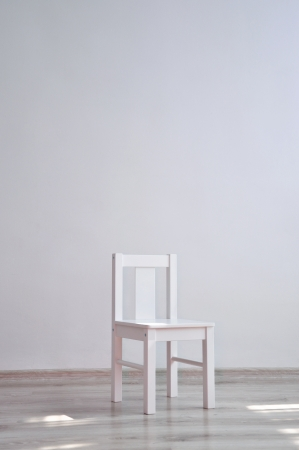 minimalistic: White geometric minimalistic style chair standing in an empty room in front of a wall on light parquet floor Stock Photo