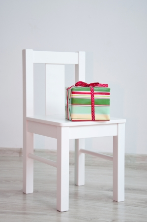 Colorful red and green celebration present with dotted ribbon and bow lying on white geometric minimalistic style chair standing in an empty room in front of a wall on light parquet floor. Natural light from the window photo
