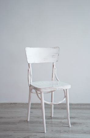 White old-fashioned retro style chair standing in an empty room in front of a wall on light parquet floor. Natural light from the window Stock Photo