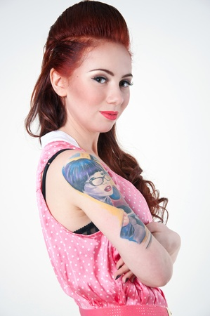 Profile portrait of pretty young woman model wearing pink dotted dress, holding her hands crossed on her chest, with high red hairstyle, big colorful tattoo on her right arm, smiling, looking at camera. Gray background, copy space photo