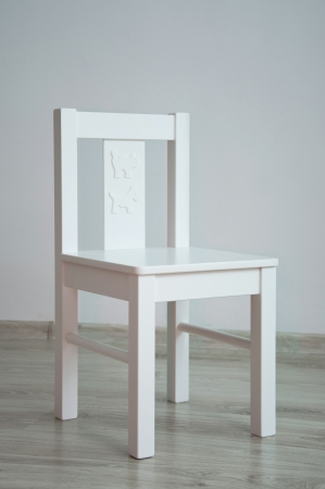 White geometric minimalistic style chair for kids with animal print standing in an empty room in front of a wall on light parquet floor. Natural light from the window