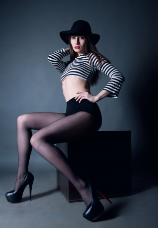 Pretty fashion brunette woman model with red lips and amazing slim long legs, wearing striped top, black short, hat and stockings sitting on a cube, holding arms on waist and head, looking at camera. Gray background